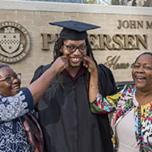 male graduate in cap and gown; his mother and aunt on either side of him pinching his cheeks
