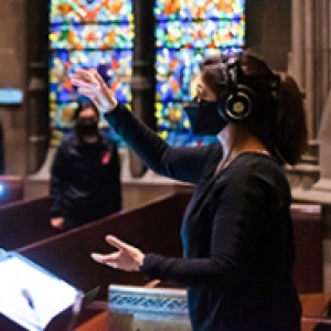 A person with headphones conducts to a socially distanced choir in Heinz Chapel