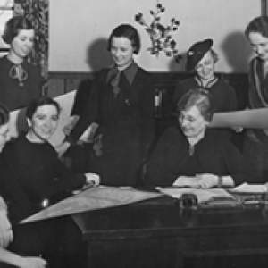 A group of women in a black and white photo sitting and standing together