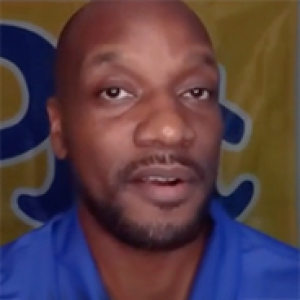 A man in a blue shirt in front of a yellow Pitt flag