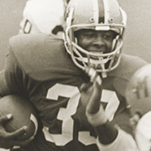 sepia image of Doresett holding a football while running