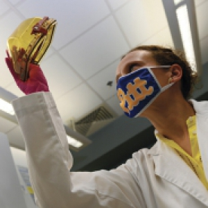 A person in a blue face mask and white lab coat holds up a gold object