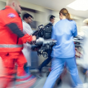 4 emergency healthcare workers see to a patient on stretcher.  The image is motion blurred.
