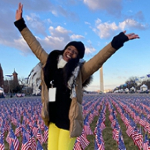 Gabriella Ogude in a black scarf and tan jacket in front of the Washington Monument