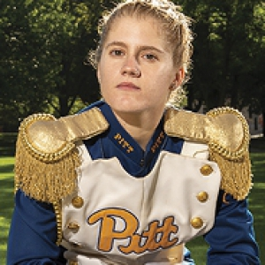 Crissy Shannon in blue and gold PItt marching band drum major uniform sitting on cement bench with baton across her lap.