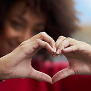 a woman in a red sweater holding her hands together in a heart shape