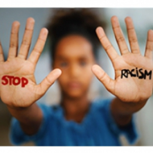 "A person in a blue shirt holds up their hands with the words ""Stop Racism"" written on them."