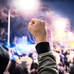 A raised fist in the air in a crowd of people on a city street