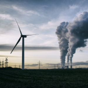 A wind turbine and smokestacks