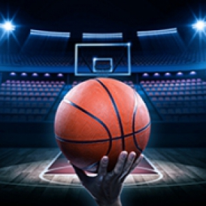 a hand holding a basketball on a spot lighted, empty court