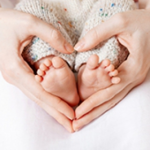 A person making a heart with their hands around a baby's feet