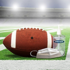 A football, a face mask and a bottle of hand sanitizer on a football field
