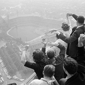A black and white photo of a crowd of people cheering as they watch a baseball game