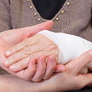 a person holding another person's bandaged hand