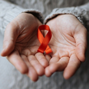 A person in a gray sweater holding a red ribbon in two hands