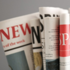 several folded newspapers over a gray background
