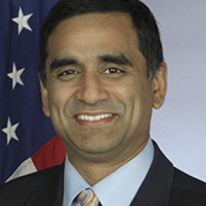 Hari Sastry headshot in front of American flag