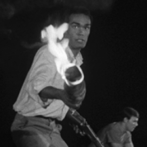 Duane Jones holds a flaming torch in a black and white image