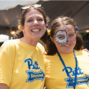 Amy Kleebank with her daughter Amelia at Staff Council's Pitt Day at Kennywood, wearing bright yellow Pitt shirts. Amelia has face painting on her right eye.