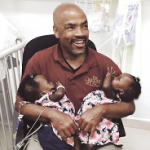 Henri Ford sitting in a red shirt, holding twins in pink dresses