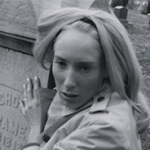 a black and white image of a woman gripping a tombstone