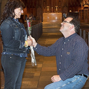 man on knee holding a rose up to a standing woman