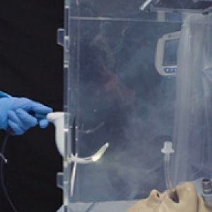 a blue-scrubbed person putting an intubation device into a clear box with a mannequin inside