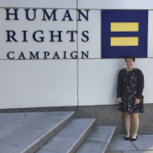 Kelley in front of an HRC logo on a building