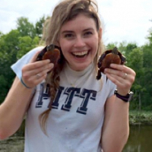 Jess Boddy, in a Pitt t-shirt, holds two turtles. A pond is in the background.