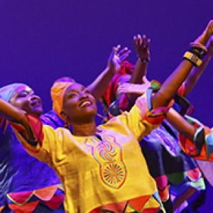 The KanKouran West African Dance Company dancing on stage in bright yellow and orange attire.