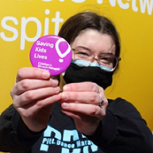 "a person in a black sweatshirt and black mask holding a pink button that says ""Saving Kids Lives"""