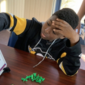 A child in a black and gold sweatshirt reaches for a board on a table