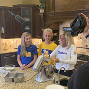 Heather Lyke with two children in Pitt shirts bake in a kitchen together while a camera crew films