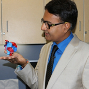 A man in a light suit and blue shirt holds a heart model