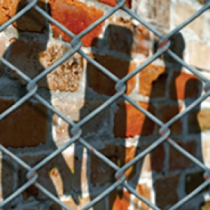 A chainlink fence in the foreground with a brick wall and the silhouettes of at least 5 people in the background