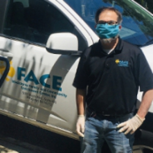 Justin LeWinter in a blue face mask standing next to a truck and a pile of cardboard boxes