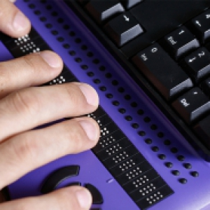 A person types on a purple Braille keyboard