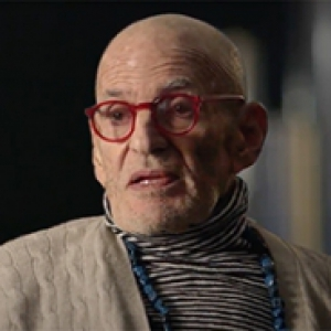 Larry Kramer in a beige sweater and striped turtleneck