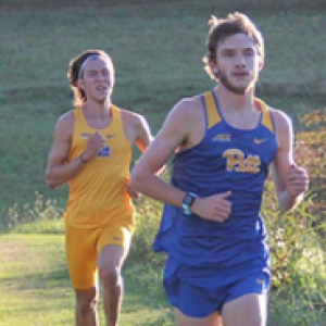 Two runners in Pitt attire in a field