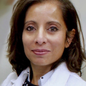 headshot of Maliha Zahid, wearing white lab coat