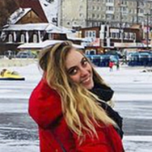 Marjorie Tolsdorf in red coat standing on ice in front of buildings in Russia