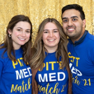 Three students in blue Pitt Med Match t-shirts.  Behind them is a gold background.