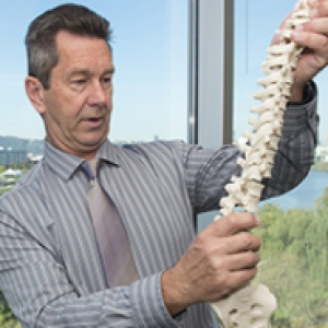 Mike Schneider examines a model human spine