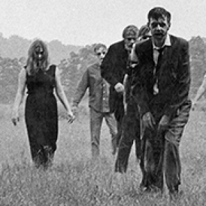 "Black and white film still from ""Night of the Living Dead"" showing several zombies crossing a field"