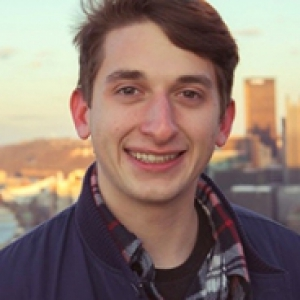 Jeremy Olin in a jacket in front of the Pittsburgh skyline