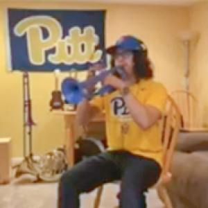A person plays multiple instruments with a Pitt banner backdrop