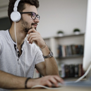 A person in a white shirt sits at a computer with headphones on