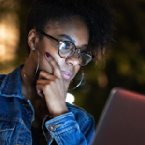 Woman with her hand on her chin looking at a laptop