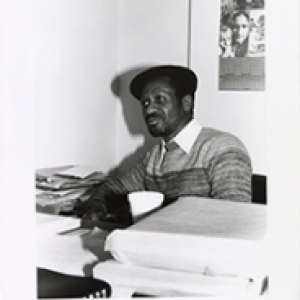 Black and white image of Rob Penny sitting at a desk.