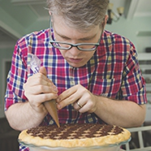 Pitt alumnus Chris Taylor in plaid shirt, using a pastry bag to finish work on a peanut butter checkerboard pie